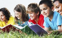 Foto van kinderen die in het gras liggen en een boek lezen.